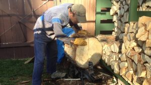 Man Splitting a big log on an electric splitter
